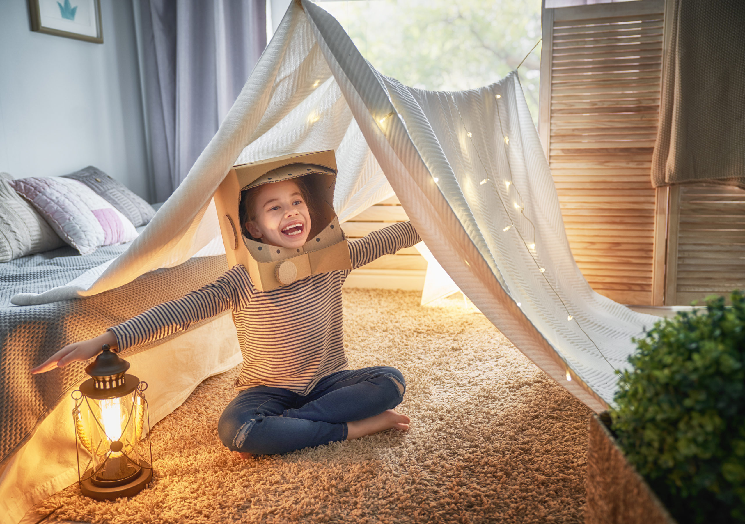 Child in an astronaut costume dreaming of becoming a spacemen. Happy kid playing in tent. Funny lovely girl having fun in children room.