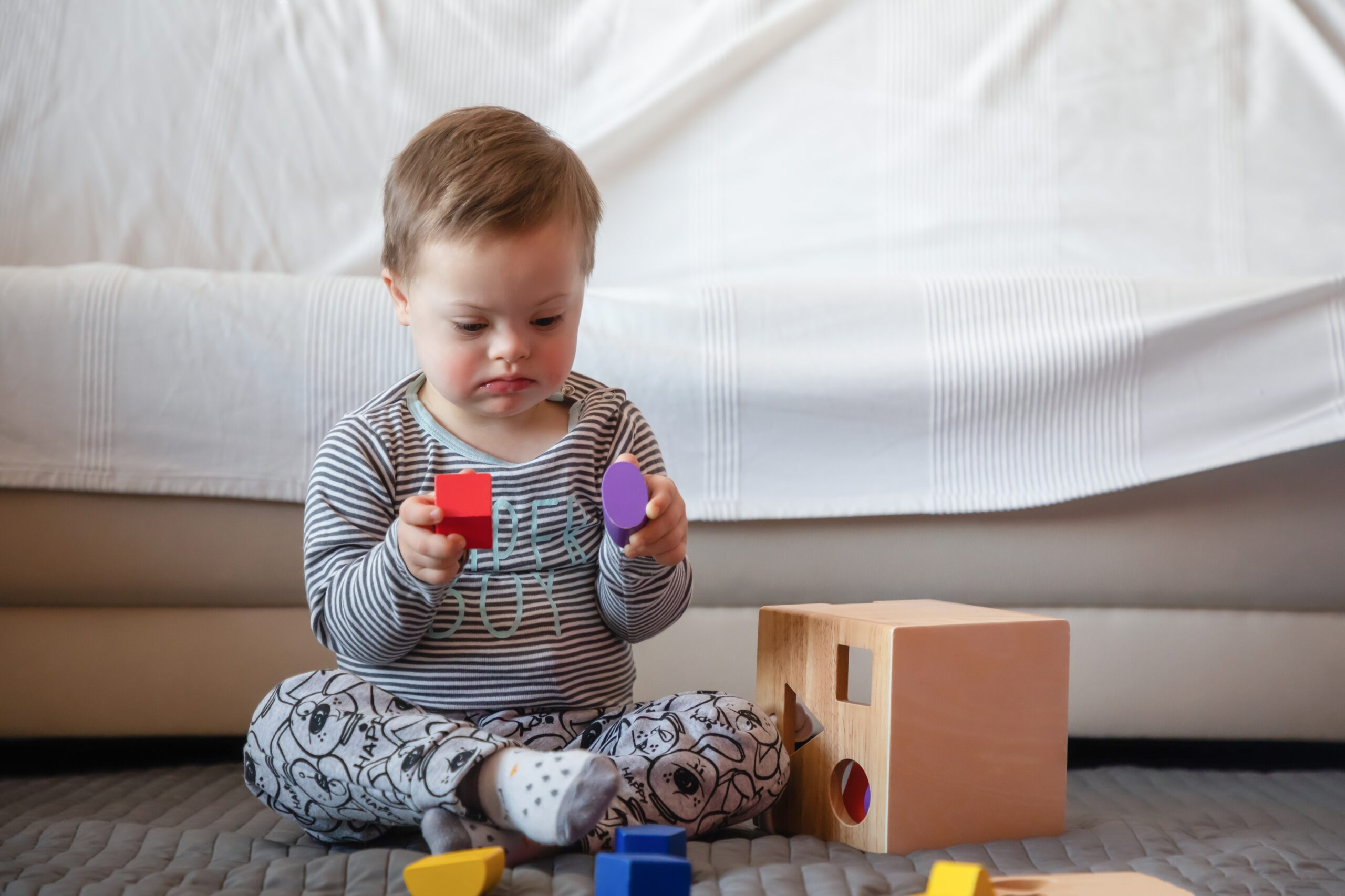small-boy-with-down-syndrome-playing-with-toys-HWPJWCU-scaled
