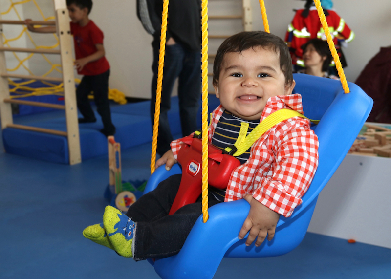 Smiling boy in blue swing