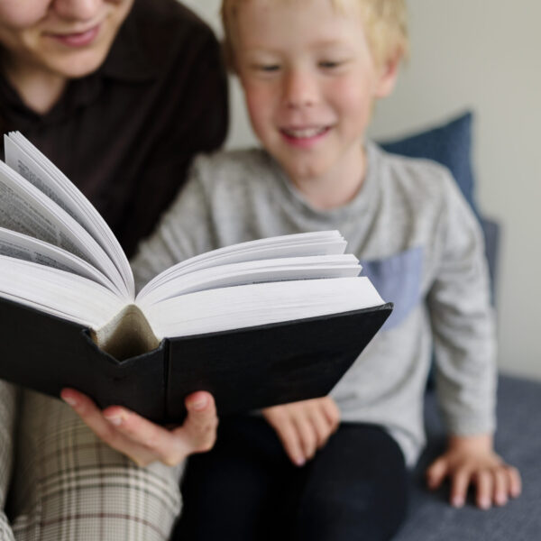 Mother and child reading book and smiling. Happy family time together