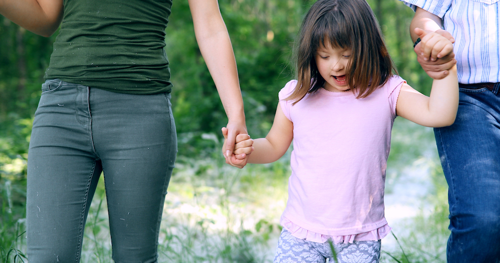 Little girl walking and holding parents hands