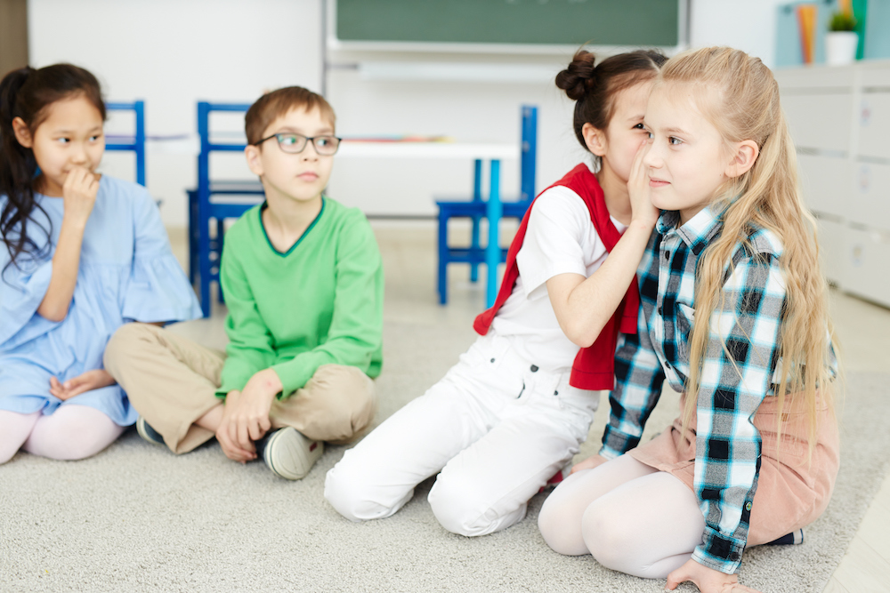children sitting and playing telephone game